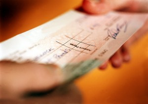 Business owner handing cheque to employee as reimbursement for expenses